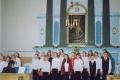 """Jaunlutriņu pamatskolas koris uzstājas Lutriņu baznīcā """"Sakoptākais Saldus rajona pagasts 2004"""" noslēguma pasākumā 2004. gada 10. augustā"""